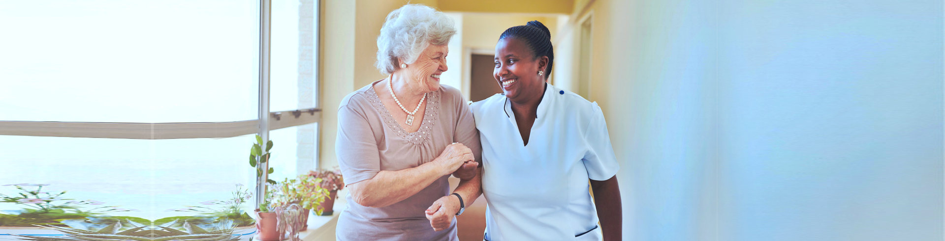 Portrait of smiling home caregiver and senior women walking together through a corridor