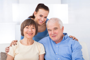 Portrait of happy female caregiver with senior couple at nursing home